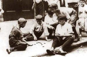 Jugar en grupo. Foto de varios niños jugando a las chapas