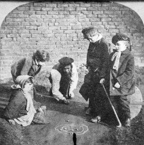 Jugar en grupo. Foto de varios niños jugando con las canicas