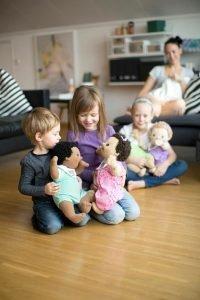 Varios niños aprendiendo a jugar con muñecas