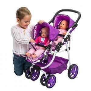 Foto de una niña jugando con un carrito de muñecas y dos muñecas
