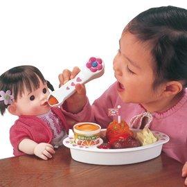 Foto niña aprendiendo a jugar con muñecas y comida