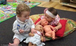 Foto de dos bebés aprendiendo a jugar con muñecas