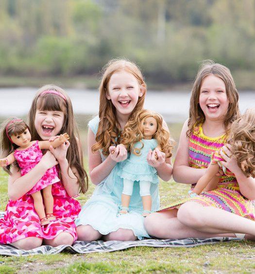 Foto de tres niñas aprendiendo a jugar con muñecas
