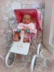 Foto de bebé reborn con una sillita big rosa de Bebelux
