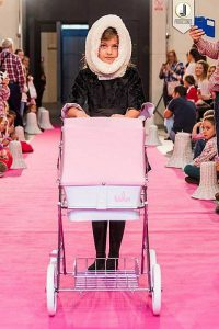 Foto de una modelo de ropa infantil en un desfile con un cochecito rosa de Bebelux