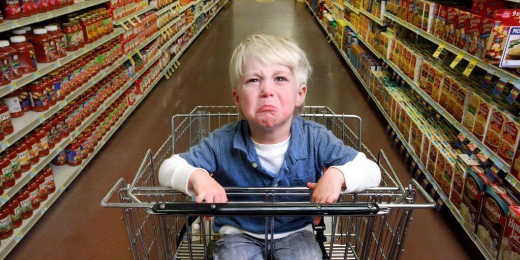 Foto niño llorando en el carro de la compra de un supermercado