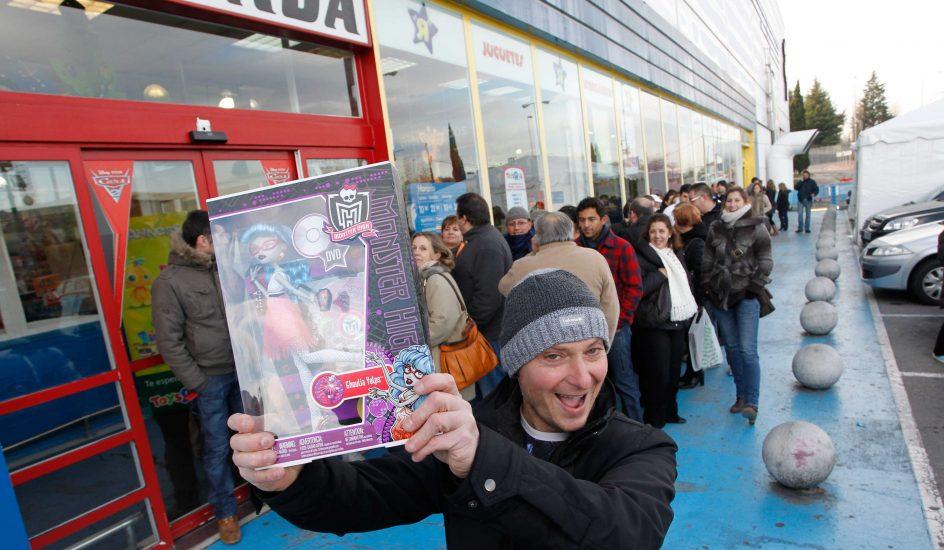 Foto de un padre en la entrada de una tienda con una de las muñecas Monster High