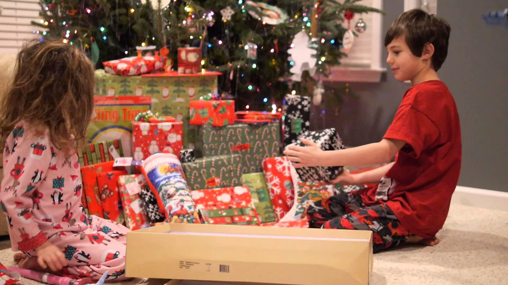 Foto de dos niños con muchos juguetes en el árbol de Navidad